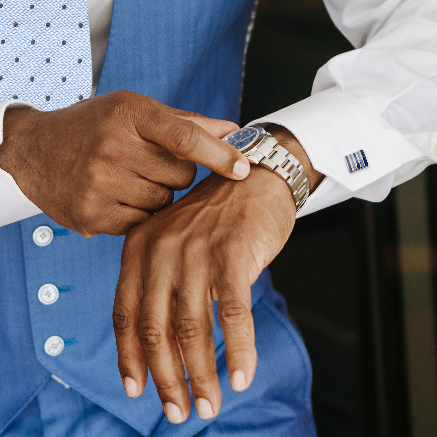 African American groom adjusting watch with cufflinks on